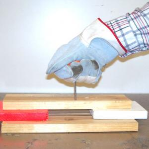 Place a pine board in an elevated position on two supporting blocks.  Also add a back stop to protect the table in case the nail completely penetrates the pine board.  Put on a leather glove, grip the small block in your hand, and place the head of the nail between the 3rd and 4th finger with the point sticking out and the nail head against the block in your fist.  Swing your hand in a large overhand motion and drive the nail into the board.