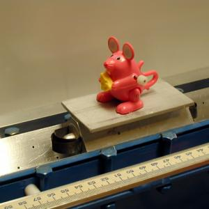 Wind up the jumping figure of choice.  Place it on the car and push it toward the end of the track.  Notice that the figure will jump up and down and still land on the car until the car bounces off the end of the air track.