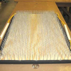 Set one bed of nails on a table or the ground, place the pillow where your head will rest, and then have someone help lower you down onto the bed.